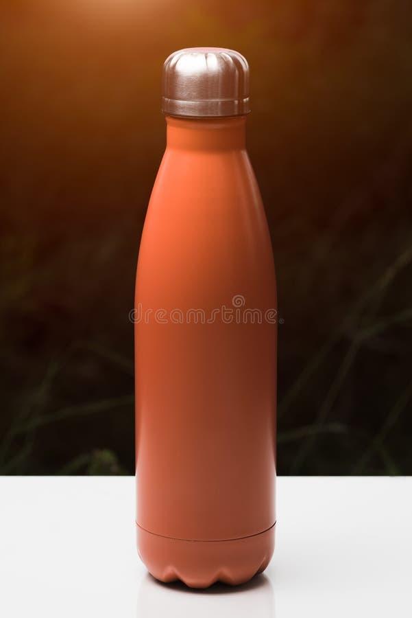 Roestvrije thermofles voor water, thee en coffe, op witte lijst Donkere grasachtergrond met zonlichteffect Thermosflessen oranje  stock afbeeldingen