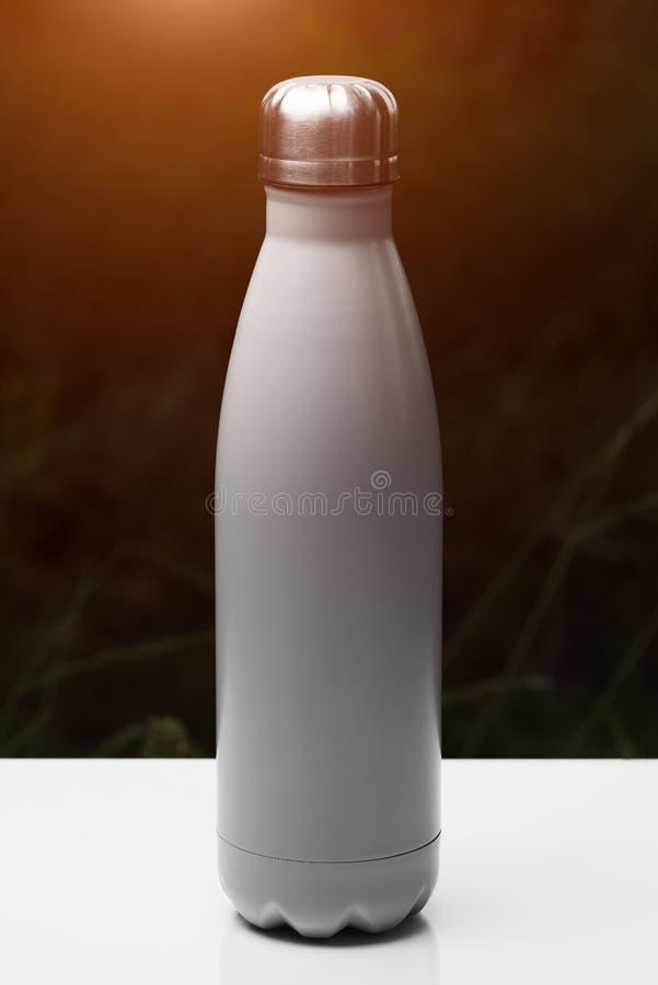 Roestvrije thermofles voor water, thee en coffe, op witte lijst Donkere grasachtergrond met zonlichteffect Thermosflessen zilvere royalty-vrije stock afbeelding