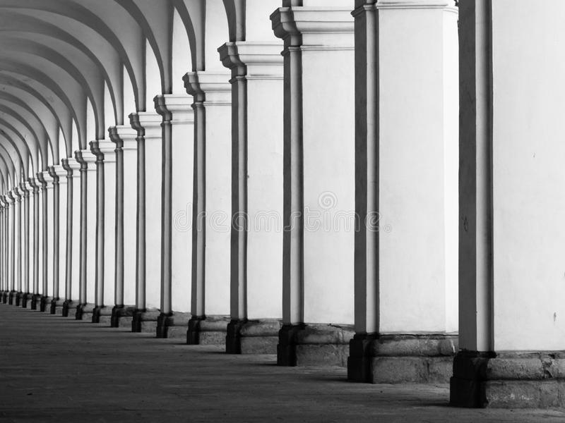 Rof of columns in colonnade. Row of column in colonnade. Perspective view of long arc vault corridor. Black and white image stock images