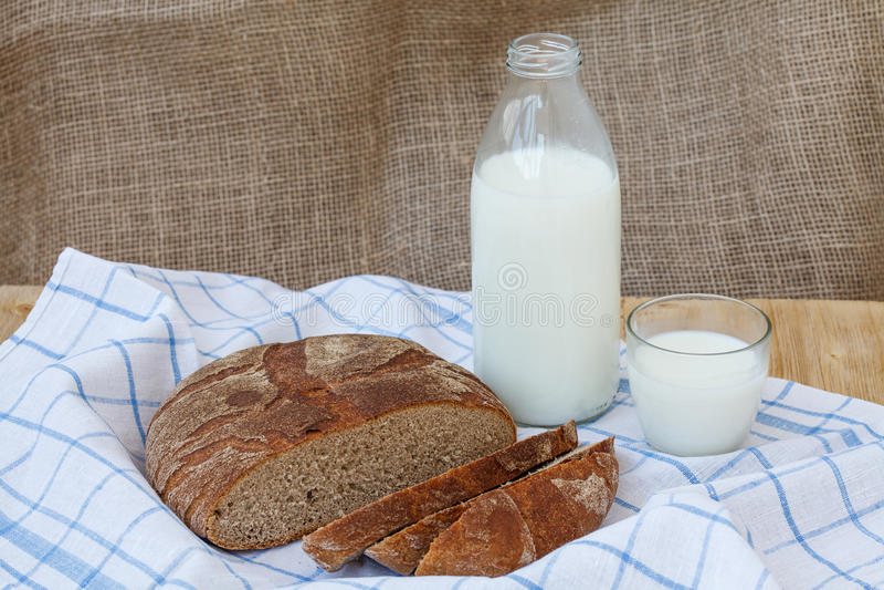Rogge gesneden brood met fles melk op houten lijst stock afbeelding