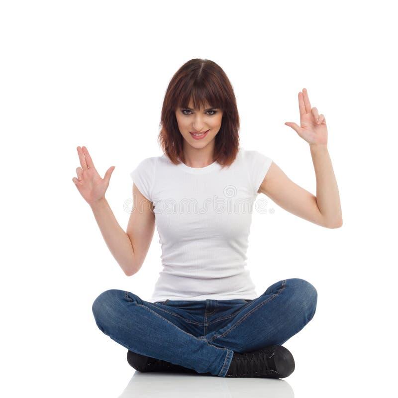 Rogue Young Woman Is Sitting su un pavimento, tenente arma alzato e mostrando il segno della mano della pistola immagini stock