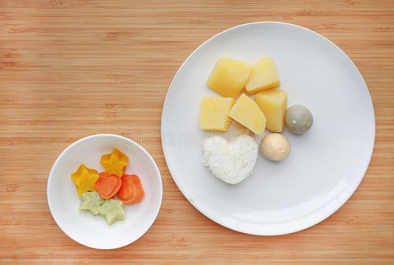 Roh von gekochtem Gemüsesäuglingsnahrungsei, -kartoffel und -reis in der weißen Platte mit der gefrorenen gestampften Säuglingsna stockbilder