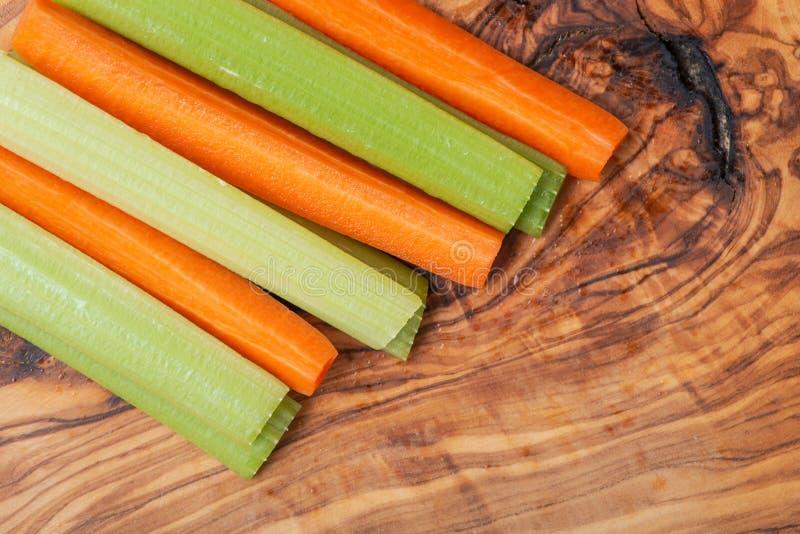 Roh zog ab und schneidet organische Sellerie-Stiele und orange den Karotten, die auf olivgrünem Holz vereinbart wurden Apiaceae-  lizenzfreie stockfotografie