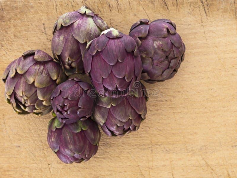 Rohe Artischocken, Mittelmeergemüse, ungekocht auf hölzernem Brett nahaufnahme stockfotos