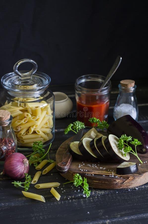 Rohe Bestandteile für das Kochen von italienischen Teigwaren mit Aubergine - penne Teigwaren, Aubergine, Zwiebel, Tomatensauce, G lizenzfreies stockbild