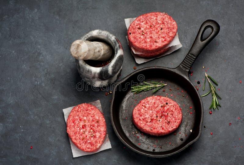 Rohe Burgerkoteletts vom Rindfleischfleisch mit mit Pfeffer und Rosmarin stockfotografie
