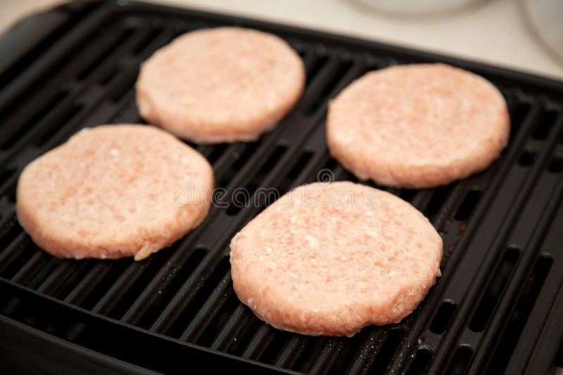 Rohe die Türkei-Burger auf Grill lizenzfreie stockbilder