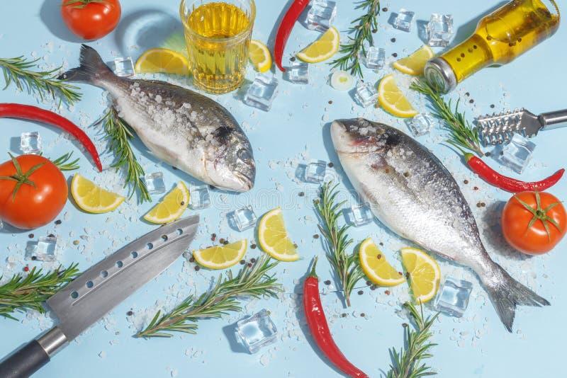 Rohe dorada Fische mit Gewürzen, Salz, Zitrone und Kräutern, Rosmarin auf einem ligth-blauen Hintergrund Beschneidungspfad einges stockbild