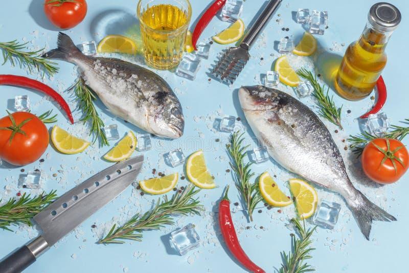 Rohe dorada Fische mit Gewürzen, Salz, Zitrone und Kräutern, Rosmarin auf einem ligth-blauen Hintergrund Beschneidungspfad einges lizenzfreies stockbild