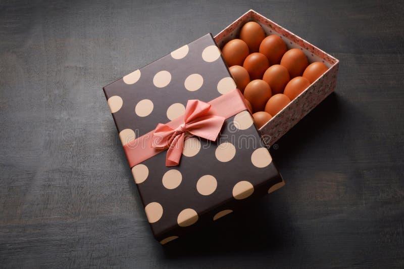 Rohe Eier in einer halb offenen Geschenkbox auf schwarzem Hintergrund lizenzfreies stockfoto
