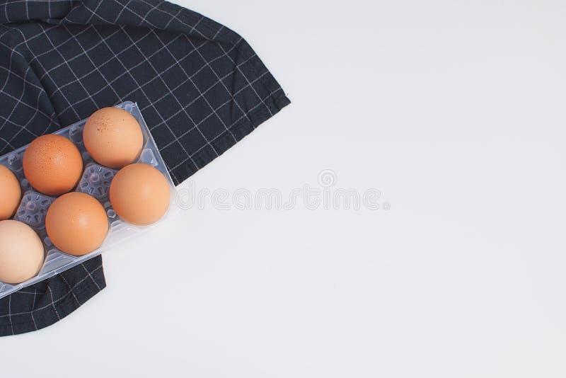 Rohe Eier und karierte schwarze Serviette minimales Bild-Weiß Backgr lizenzfreies stockfoto