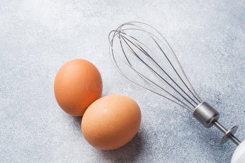 Rohe Eier und Schneebesen Browns für das Peitschen auf grauem Hintergrund lizenzfreies stockfoto