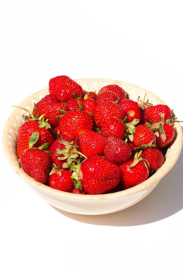 Rohe Erdbeeren, die in der Platte lokalisiert auf weißem Hintergrund liegen stockfotos
