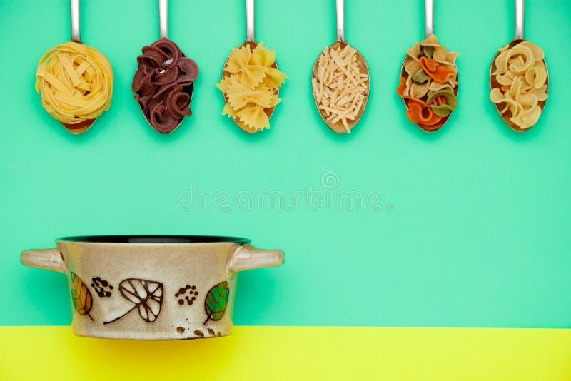 Rohe farbige Bandnudeln, Spaghettis und Teigwaren auf den Metalllöffeln auf Grün lokalisiert, schwarzer Topf auf gelbem flachem S stockfoto