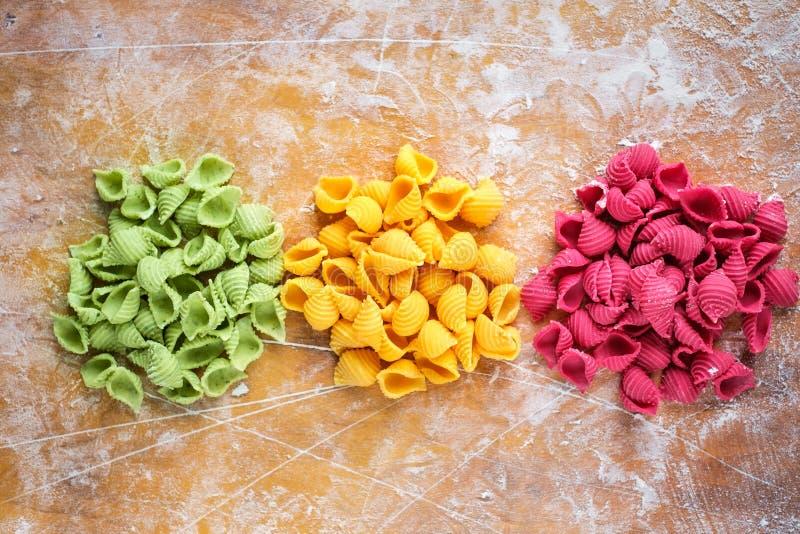 Rohe farbige Teigwaren auf dem Küchenholztisch mit Mehl, Draufsicht stockbild