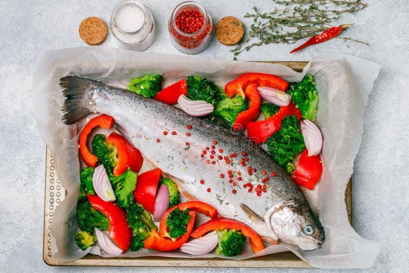 Rohe frische ganze Fischlachse, Forelle mit Gemüse stockbilder