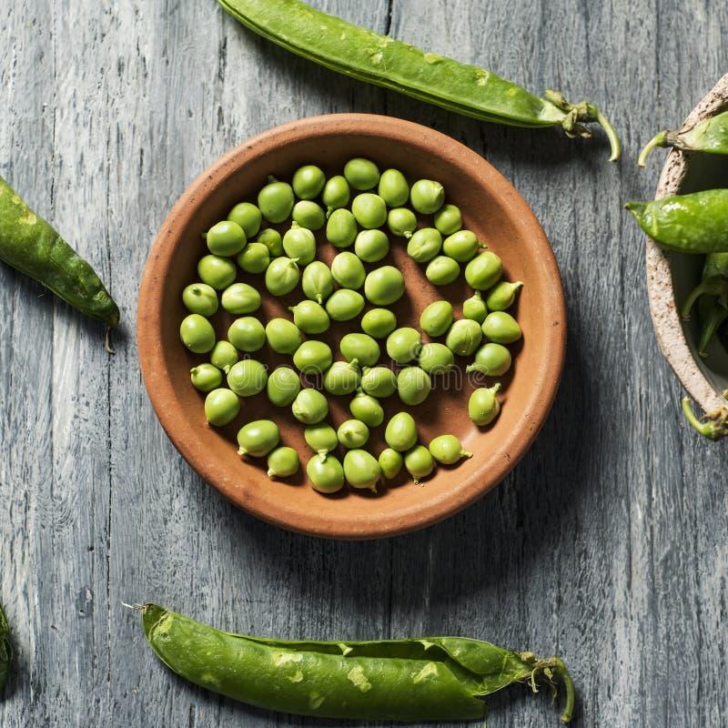 Rohe frische grüne Erbsen auf einer Tabelle stockfotografie