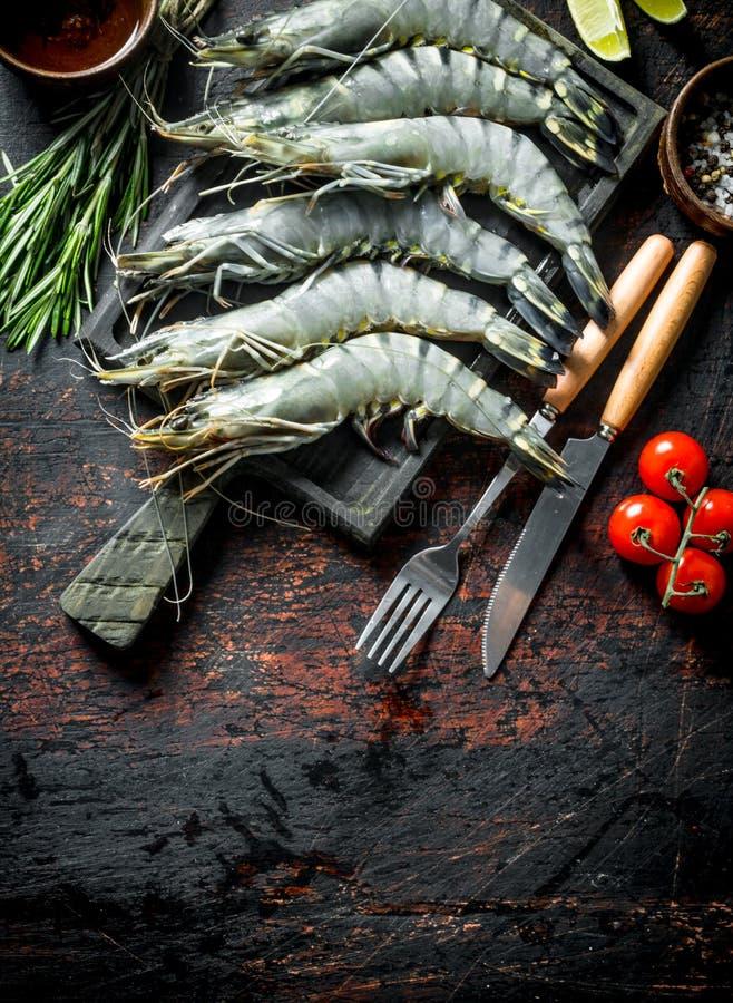 Rohe Garnelen ungekocht mit Tomaten und Rosmarin lizenzfreies stockbild