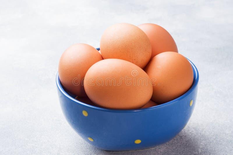Rohe Hühnereien Browns in einer blauen Schüssel auf einem grauen Hintergrund stockbild