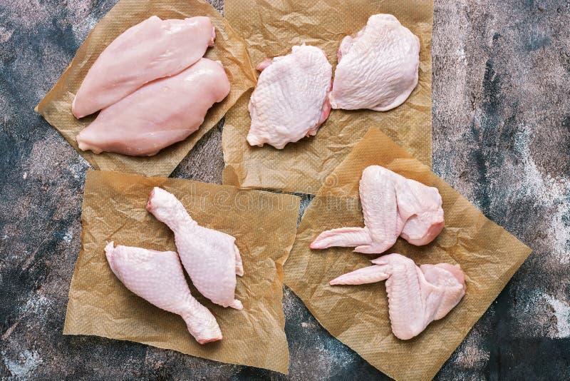 Rohe Hühnerfleischleisten, -flügel, -schenkel und -beine Rustikaler Hintergrund Ansicht von oben, flache Lage lizenzfreies stockfoto