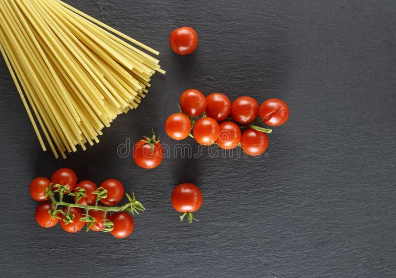 Rohe italienische lange Teigwaren und reife rote Kirschtomaten stockfotografie