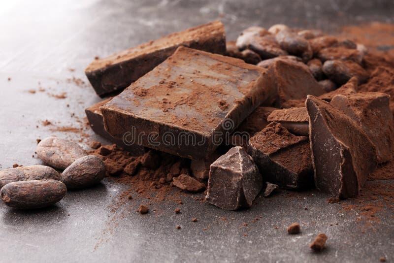 Rohe Kakaobohnen, Kakaopulver und Schokoladenstücke lizenzfreie stockfotografie