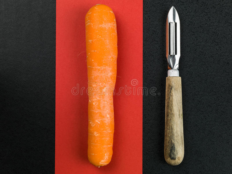 Rohe Karotte mit einem Gemüse-Peeler lizenzfreie stockfotografie
