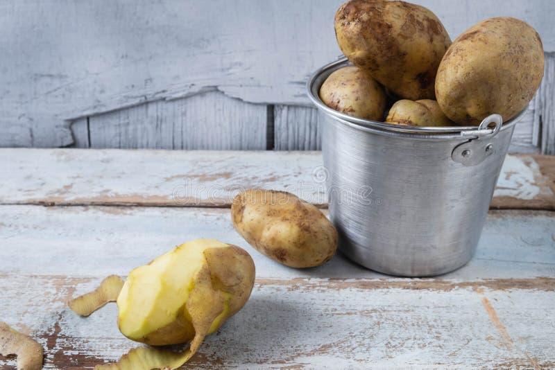 Rohe Kartoffeln auf einem hölzernen Hintergrund stockfotografie