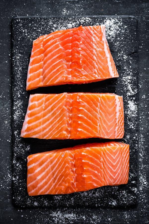 Rohe Lachsleiste auf dunklem Schieferhintergrund, wilder atlantischer Fisch lizenzfreie stockfotos