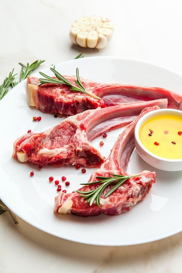 Rohe Lammrippen mit Bestandteilen für das Kochen auf weißer Marmortabelle stockbild