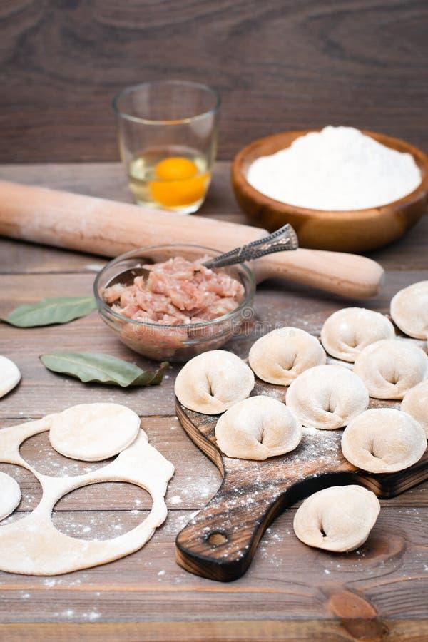 Rohe Mehlkl??e auf dem Schneidebrett und Bestandteile f?r ihre Vorbereitung: Mehl, Ei, Hackfleisch lizenzfreie stockbilder