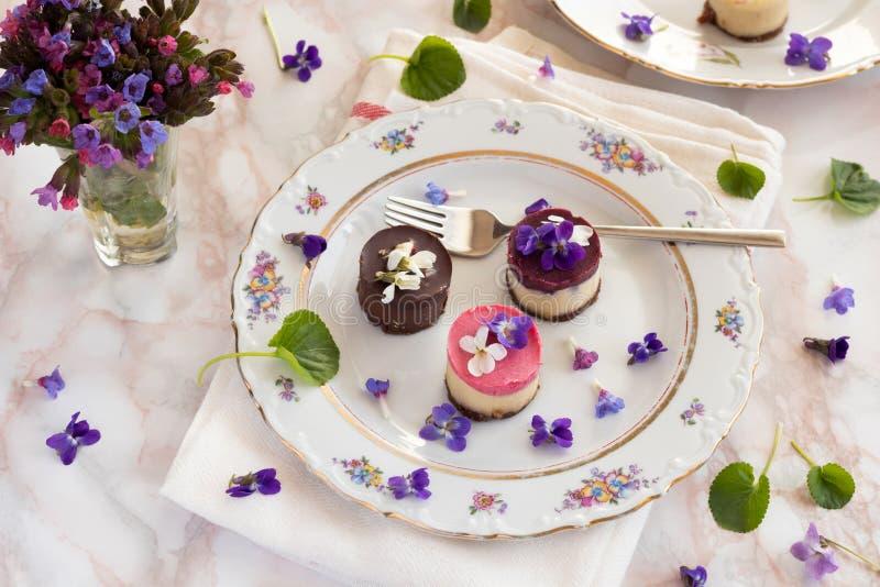 Rohe Nachtische des strengen Vegetariers mit frischen violetten Blumen lizenzfreies stockbild