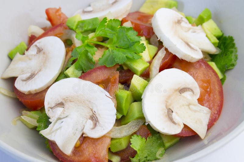 Rohe Nahrung des Frischgemüsesalattomatenavocado-strengen Vegetariers mit rohen Champignons, vermehren sich rohes Gemüse mit Oliv stockfotografie
