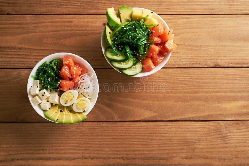 Rohe organische Stoß-Schüssel mit mit Reis, Avocado, Lachs, Mango, Gurken, chuka Salat, Wachteleier, süße Plattennahaufnahme der  stockfoto