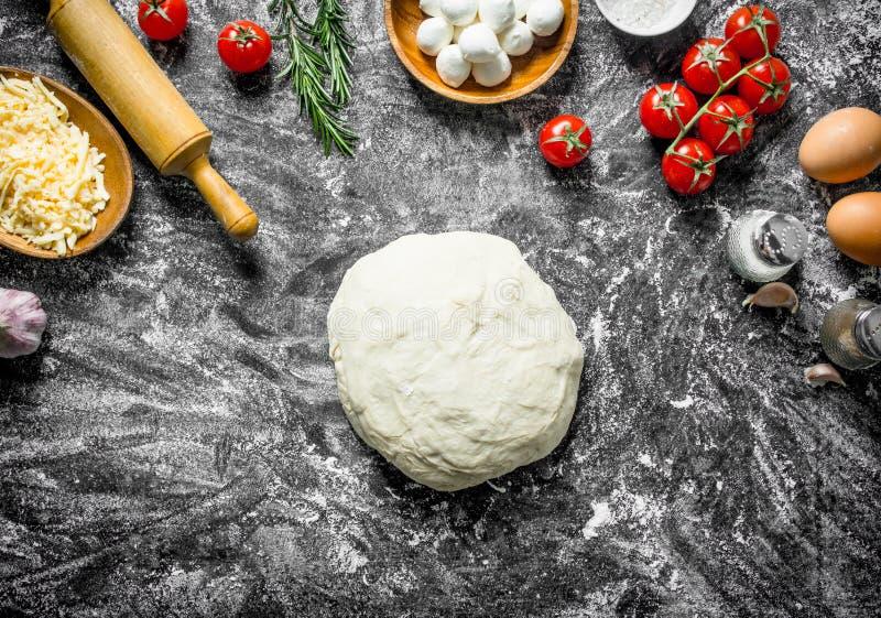 Rohe Pizza Teig mit verschiedenen Bestandteilen für das Kochen der selbst gemachten Pizza stockfotografie