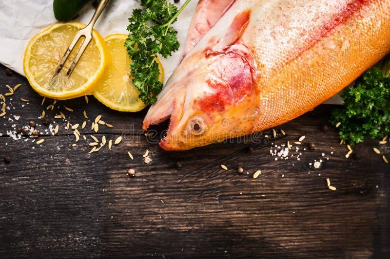 Rohe Regenbogenforelle-Fischvorbereitung auf alten Holztisch lizenzfreie stockbilder