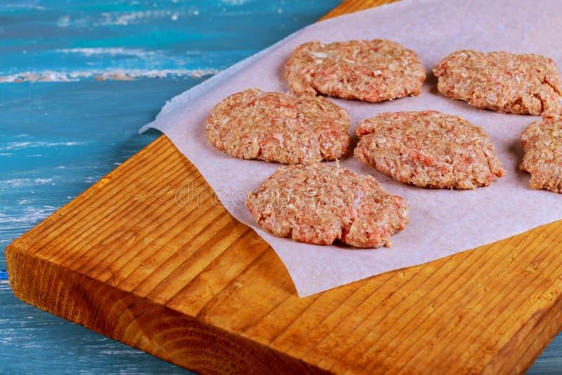 Rohe Rinderhackfleischfleisch Burger-Steakkoteletts mit Gewürz auf hölzernen Brettern der Weinlese lizenzfreies stockfoto