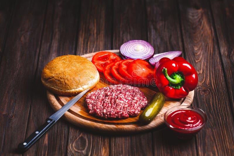 Rohe Rinderhackfleischfleisch Burger-Steakkoteletts mit Gewürz, Käse stockfoto