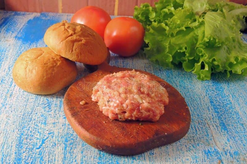 Rohe Rinderhackfleischfleisch Burger-Steakkoteletts mit Gewürz, Käse, Tomaten, Salat und Brötchen auf den hölzernen Brettern der  stockbild