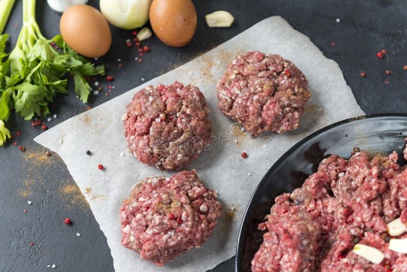 rohe Rindfleischkoteletts, Burger, Rinderhackfleisch, Gewürze, Eier, Sellerie, Knoblauch, Zwiebel lizenzfreie stockfotos
