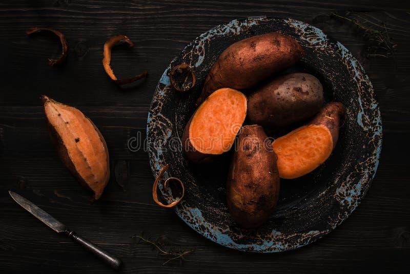 Rohe Süßkartoffel auf der hölzernen schwarzen Tischplatteansicht lizenzfreie stockfotografie