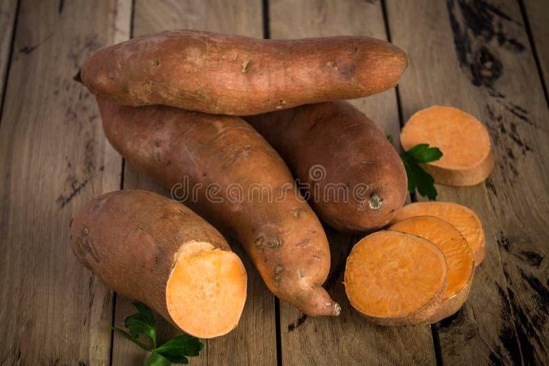 Rohe Süßkartoffeln auf rustikalem hölzernem Hintergrund stockbilder