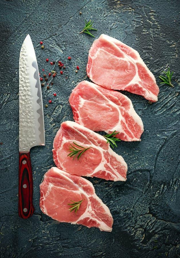 Rohe Schweinelende hackt mit Kräutern, Rosmarin, Thymian, Pfeffer und Messer stockfoto