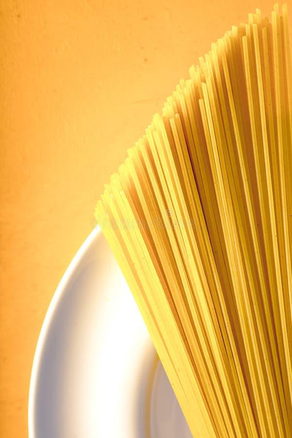 Rohe Spaghettis auf der weißen Platte auf der gelben Hintergrundvertikale lizenzfreie stockfotos