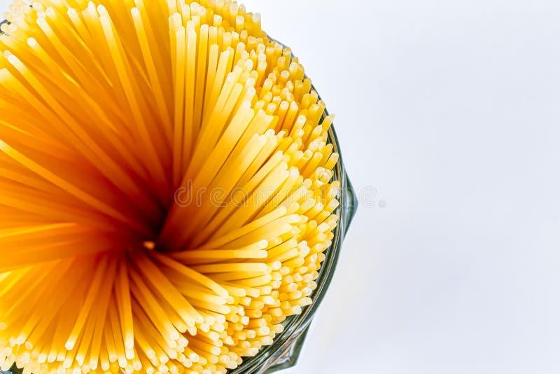 Rohe Spaghettiteigwaren - Foto eines Behälters mit einem Teil Spaghettiteigwaren angesehen von oben stockfoto