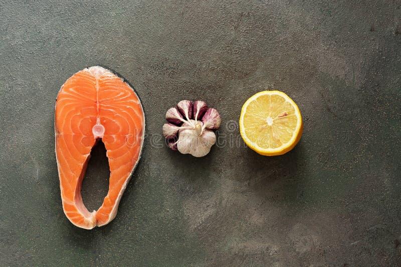 Rohe Steakfische Lachs, Zitrone und Knoblauch in Folge auf einem dunklen rustikalen Hintergrund Draufsicht, flache Lage, Kopienra lizenzfreie stockfotografie