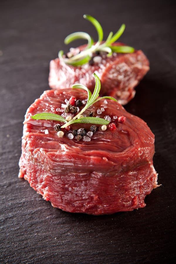 Rohe Steaks des frischen Rindfleisches auf schwarzem Stein lizenzfreie stockfotografie