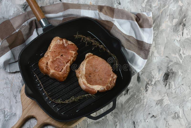 Rohe Steaks für das Grillen in einem Eisenstein Chef gießt Olivenöl über frischem Salat in der Gaststätteküche lizenzfreie stockfotos
