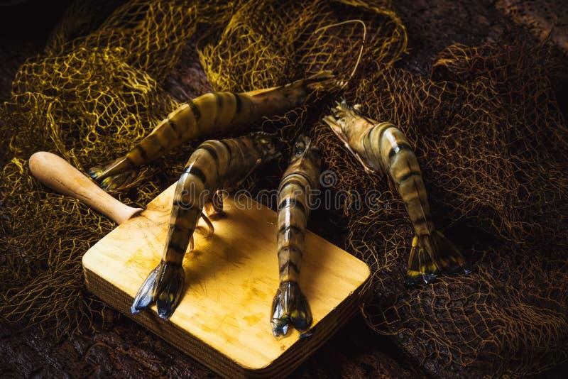 Rohe Tigergarnelen auf altem Holztisch lizenzfreies stockfoto