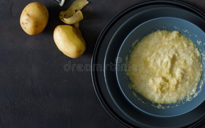 Rohe zerriebene Kartoffeln für das Kochen von Kartoffelpfannkuchen auf dunklem backgrou lizenzfreie stockbilder